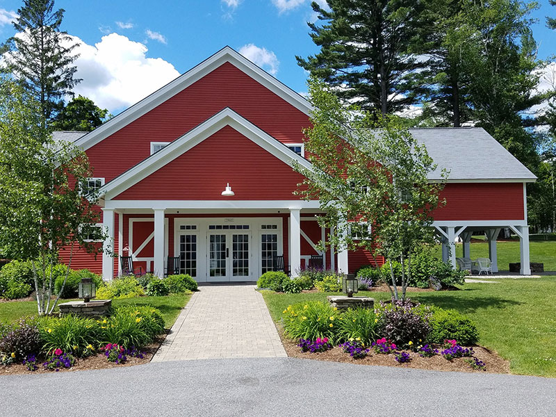 Red barn with white doors and trim with summer flowers in the beds
