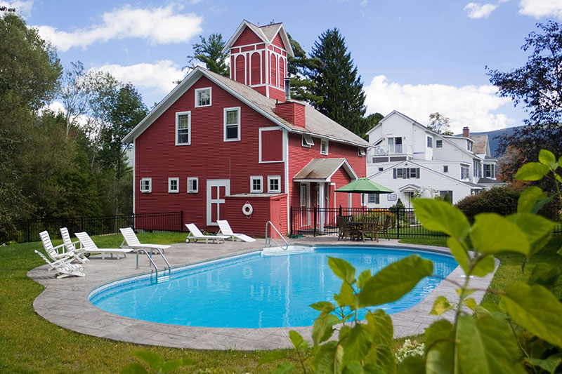 The red barn like building next to a beautiful blue inground pool